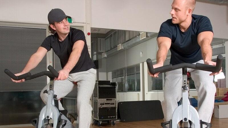 Zwei sich zugewandte Männer auf Spinningrad in Fitnessstudio