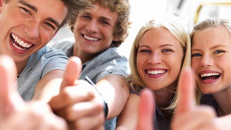 Vier Jugendliche lachen in Kamera, Daumen zeigt nach oben