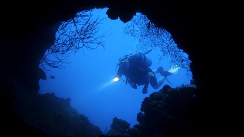Taucher vor dunkler Höhle unter Wasser mit Taschenlampe, Foto aus Höhle geschossen