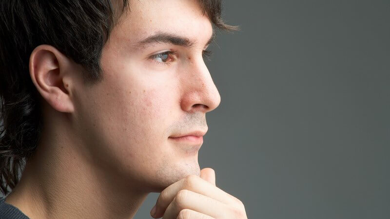 Seitenansicht Gesichtsportrait junger Mann, Hand an Kinn gelegt