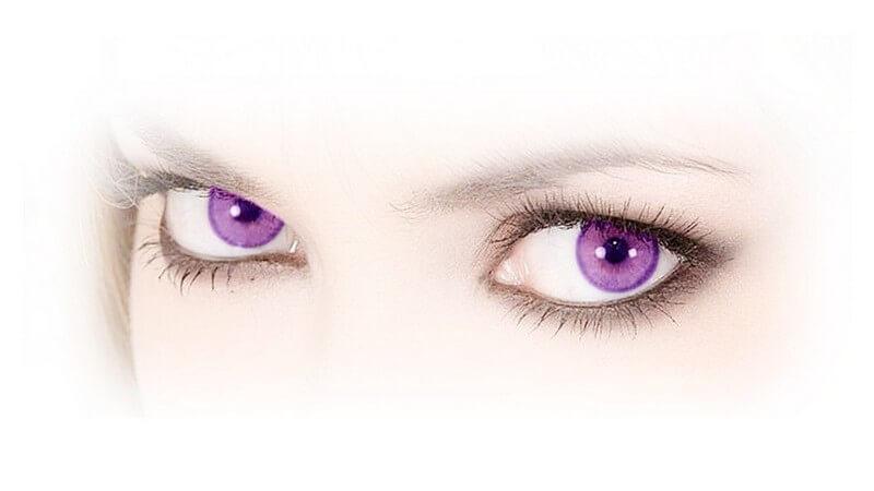 Nahaufnahme Augenpartie einer jungen Frau, geschminkt, mit lila oder violetten Augen (Farbkontaktlinsen)