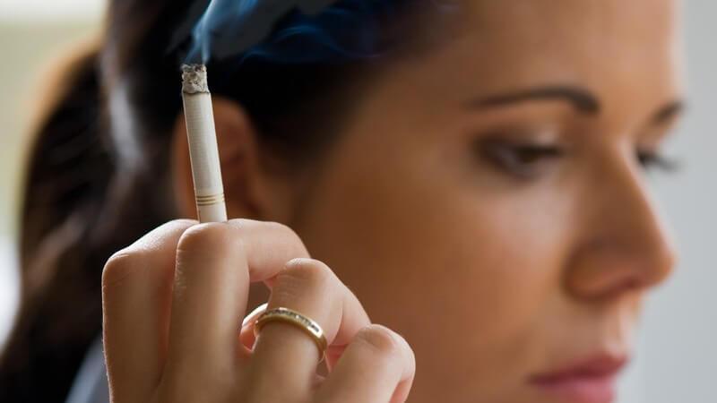 Seitenansicht junge dunkelhaarige Frau hält qualmende Zigarette in Hand