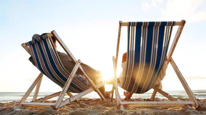 Rückansicht Paar in Liegestühlen am Strand am Meer