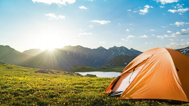 Abenteuerreisen mit Camping: Zelt in Naturlandschaft, im Hintergrund Berge und ein See