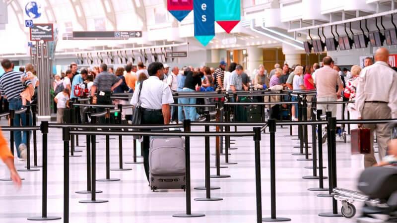 Einsicht in Flughafenhalle mit vielen menschen an Schaltern