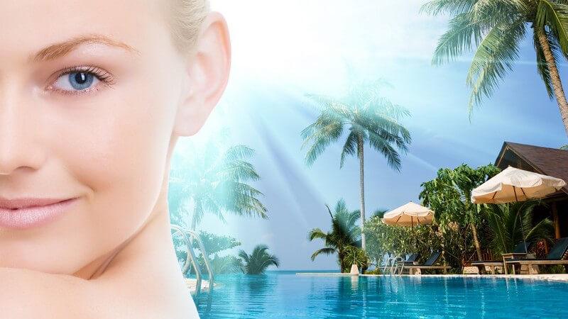 Halbes Gesicht einer Frau, im Hintergrund Pool und Palmen