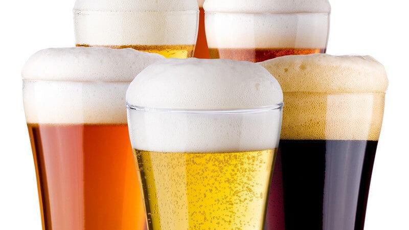 Sechs Gläser mit verschiedenen Biersorten auf weißem Hintergrund
