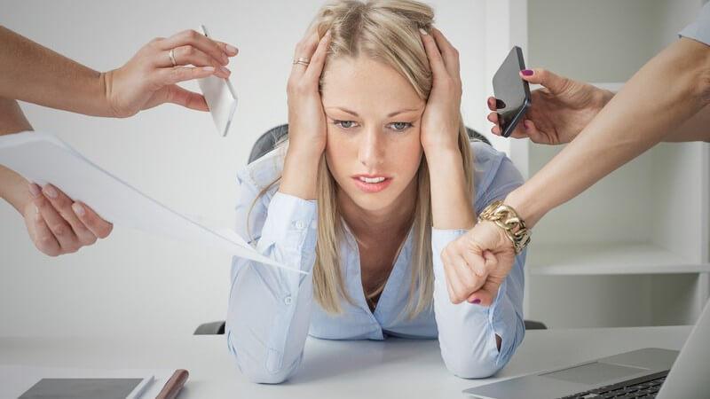 Blonde Geschäftsfrau hängt völlig gestresst auf ihrem Schreibtisch, umgeben von Kollegen-Händen mit Smartphone und Uhr