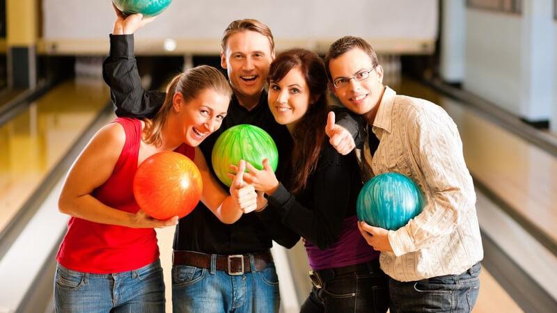 Vier Freunde mit Bowlingkugeln, lachen in Kamera