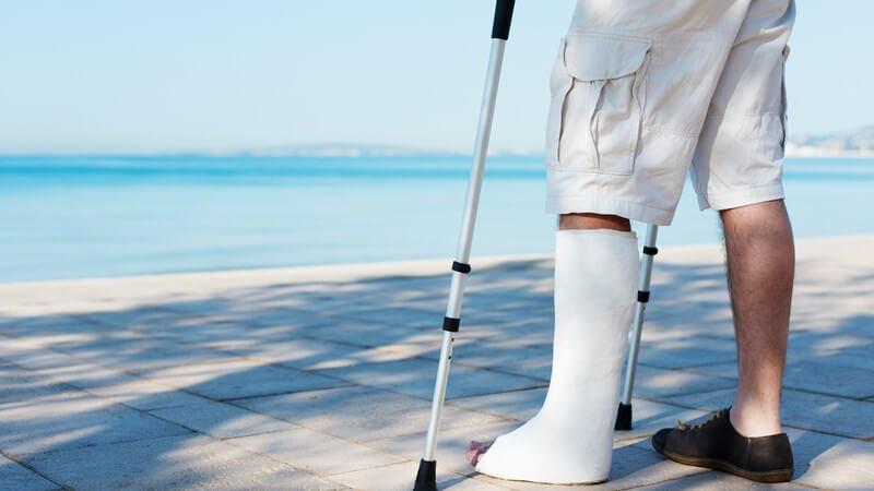 Mann mit Gipsbein am Meer, Beinbruch im Urlaub, Auslands-Krankenversicherung