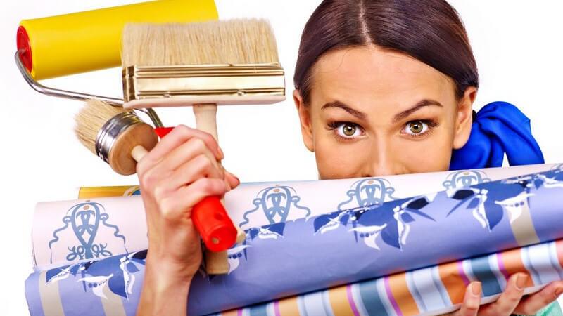 Heimwerken - Frau mit Pinsel, Farbrolle und Tapeten