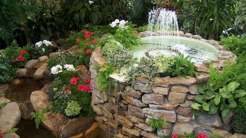Springbrunnen aus Stein mit Wasserspiel im Garten, umgeben von Pflanzen
