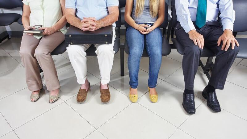 Beine mehrerer Menschen, Patienten sitzen im Wartezimmer einer Arztpraxis