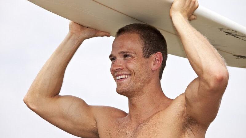 Junger Mann, oberkörperfrei, trägt mit beiden Händen Surfbrett auf dem Kopf gelehnt und lächelt