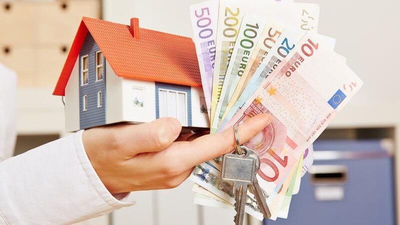 Hand im Büro hält ein Hausmodell, Euro-Geldscheine und Schlüssel