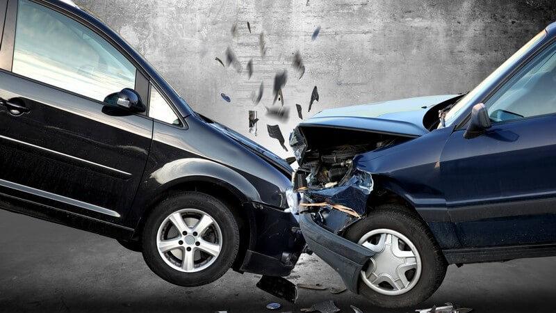 Unfall zwischen einem schwarzen und blauen Auto vor einer grauen Wand