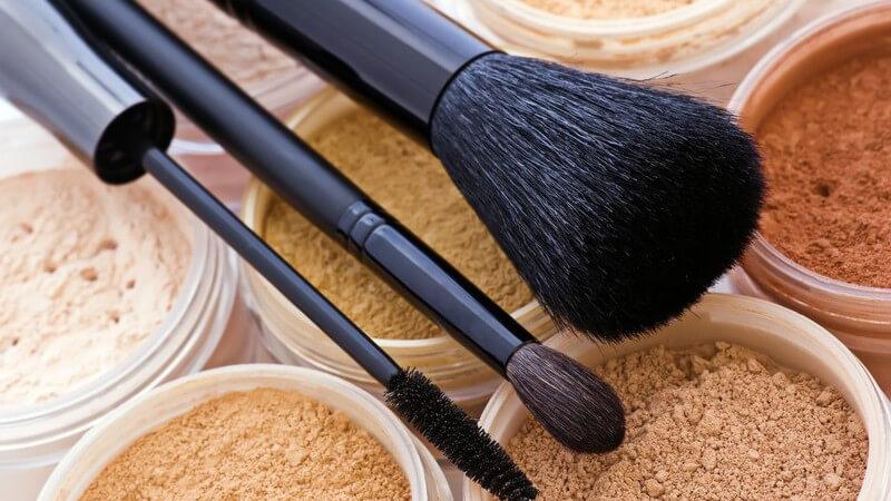 Mehrere Puderdosen in unterschiedlichen Farben, darüber liegt großer und kleiner Pinsel und Mascarabürste