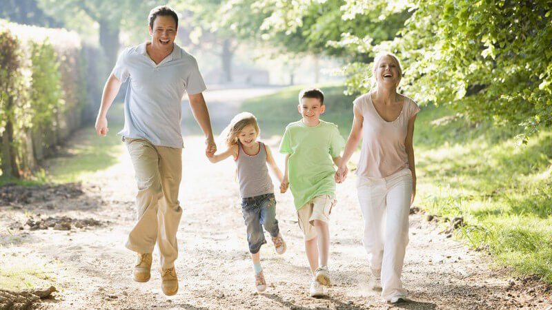 Junge Familie läuft zusammen über einen Weg
