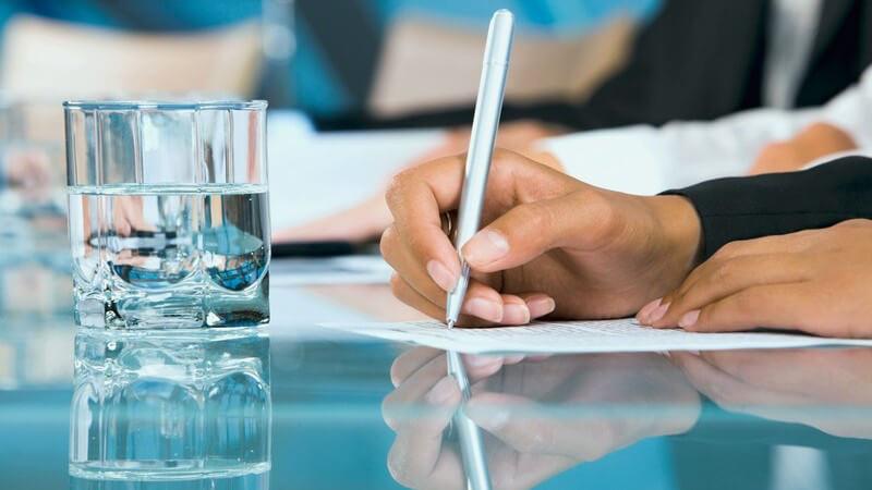 Nahaufnahme rechte Hand schreibt mit Kuli auf Papier
