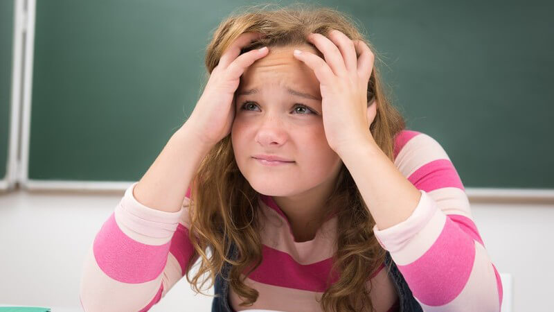 Mädchen sitzt über einem Heft im Klassenzimmer und fasst sich verzweifelt und überfordert an den Kopf