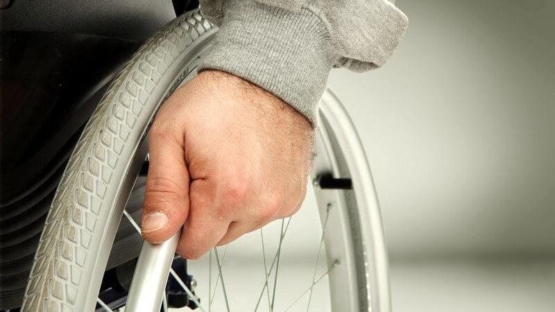 Hand am Rad eines Rollstuhls - Mensch mit Behinderung