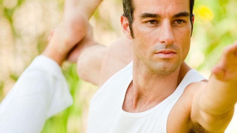 Mann in weißer Kleidung macht Yogaübung