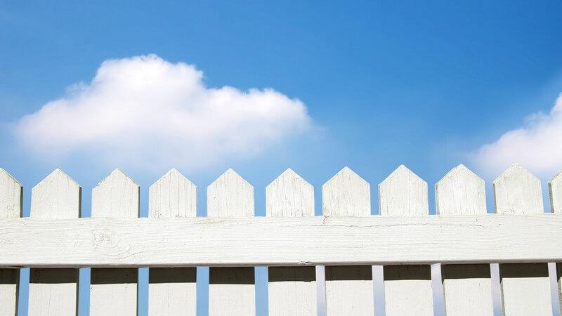 Weißer Lattenzaun unter blauem Himmel
