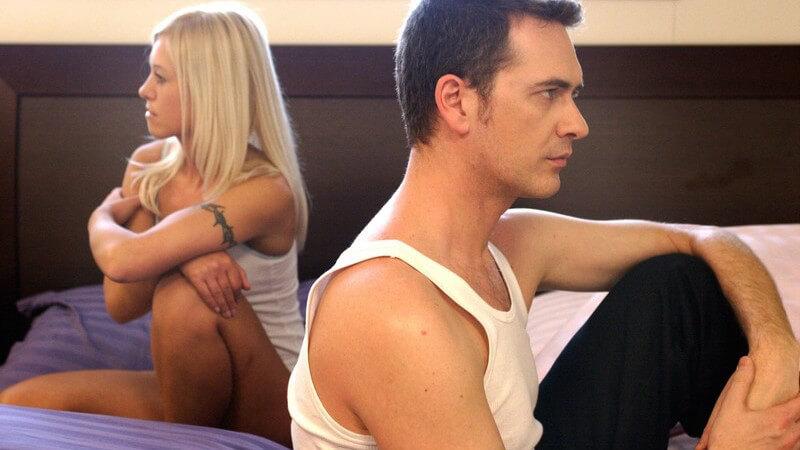 Mann und Frau sitzen auf Bett, wenden sich beide in Unterhemd den Rücken zu, schweigen