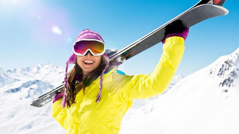 Lachende Frau in Skimontur mit Skiern auf der Schulter unter blauem Himmel mit Sonne, im Hintergrund Berge