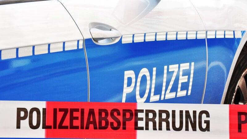 """Nahaufnahme Polizeiauto, davor Band mit Aufschrift """"Polizeiabsperrung"""""""
