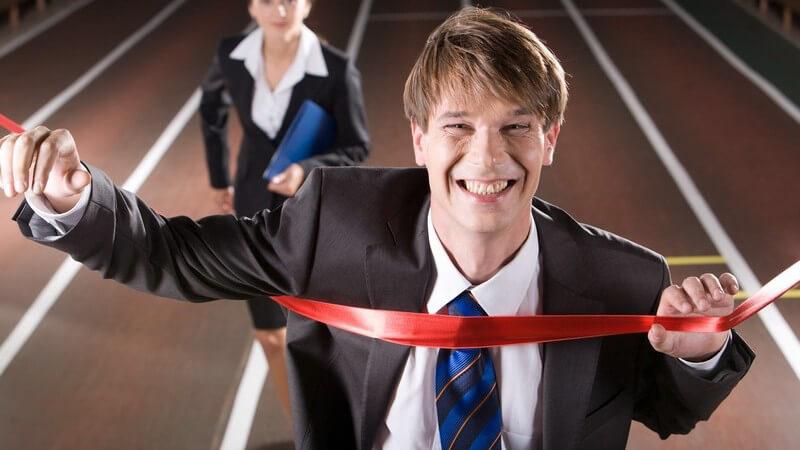 Geschäftsmann im Anzug läuft auf Laufbahn durchs Ziel