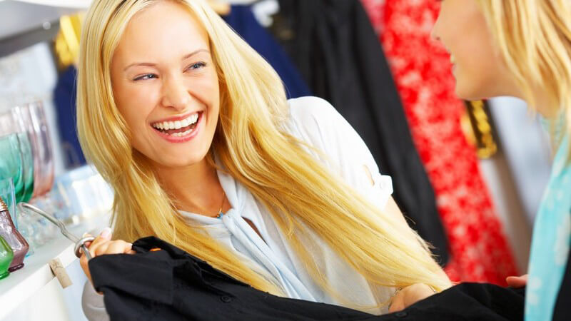 Junge Frau zeigt lachend ihrer Freundin schwarze Bluse im Geschäft