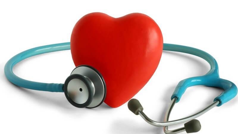 Rotes Herz aus Kunststoff, daneben Stethoskop, weißer Hintergrund