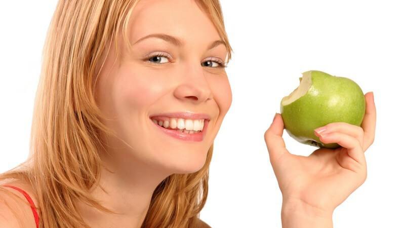Blonde Frau lächelt und hält grünen, angebissenen Apfel neben ihr Gesicht