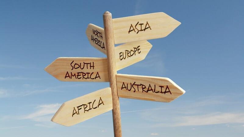 Schild mit angezeigten Richtungen in sechs Kontinente, blauer Himmel
