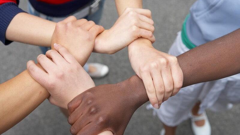 Multikulti Hände von Jugendlichen mit verschiedener Hautfarbe fassen sich zu einem Kreis oder Stern