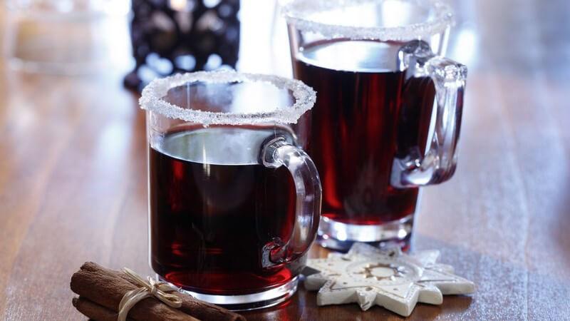 Zwei Gläser mit Glühwein auf Tisch, daneben Zimtstangen und Holzstern als Deko