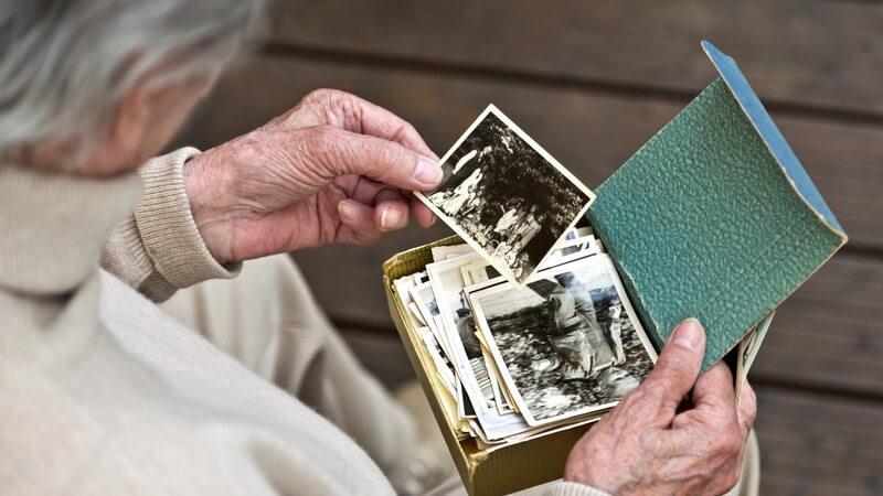 Erinnerungen an die Kindheit: alte Frau betrachtet Schwarz-Weiß-Fotos