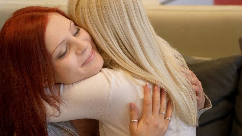 Zwei Freundinnen, rothaarig und blond, umarmen sich