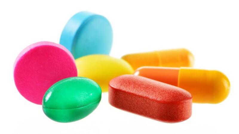 Sieben unterschiedliche und verschiedenfarbige Pillen (Drogen) vor weißem Hintergrund