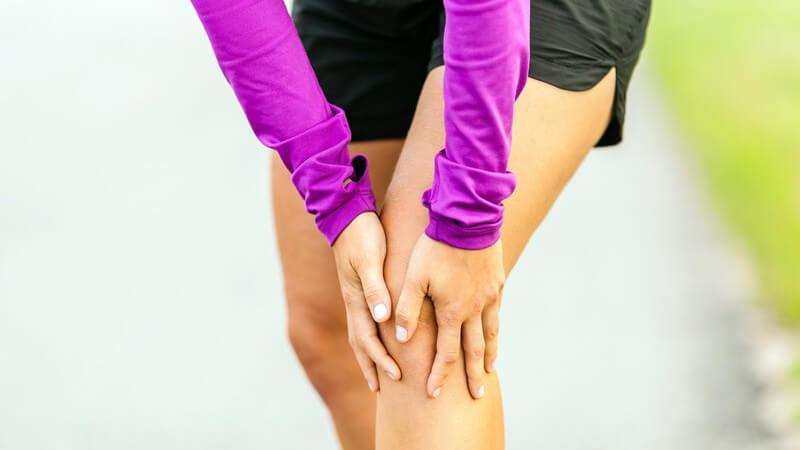 Joggerin in lila Laufbekleidung steht und fasst sich an das Knie