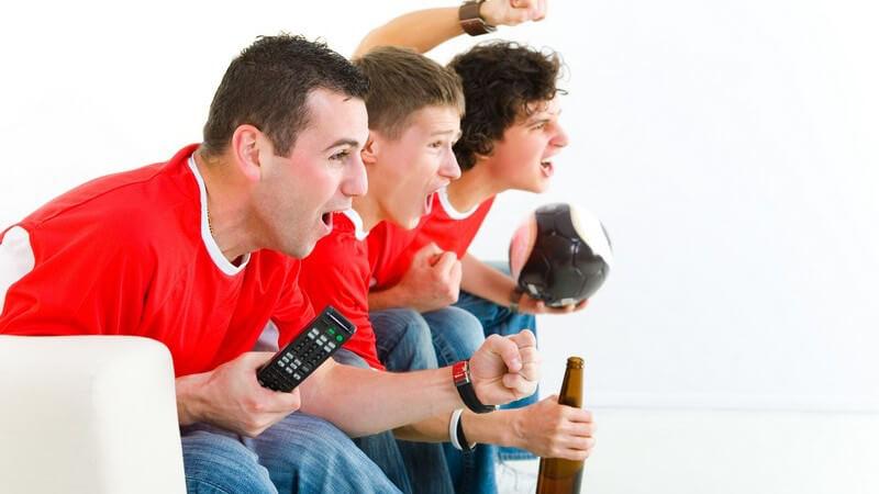 Drei junge Männer auf Couch beim Fußballgucken