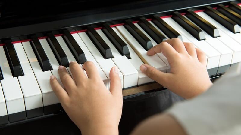 Kinderhände spielen auf einem Piano