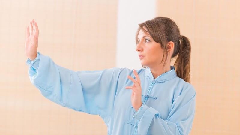 Frau in blauer Kleidung bei einer Qi Gong-Übung