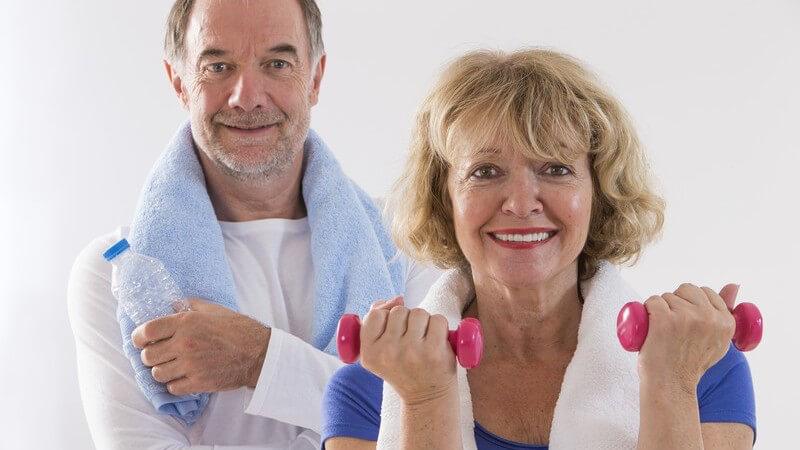 Sportliches Seniorenpaar mit Handtuch um den Hals, er mit Wasserflasche und sie mit pinken Kurzhanteln