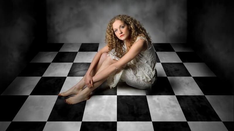Junge Frau sitzt alleine in kleinem Raum, schwarz-weiß gekachelter Boden