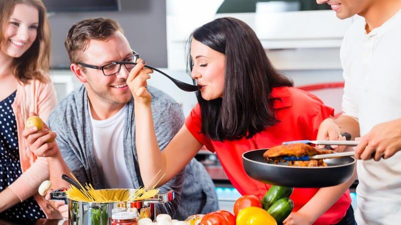 Vier Freunde beim gemeinsamen Kochen von Pasta und Fleisch