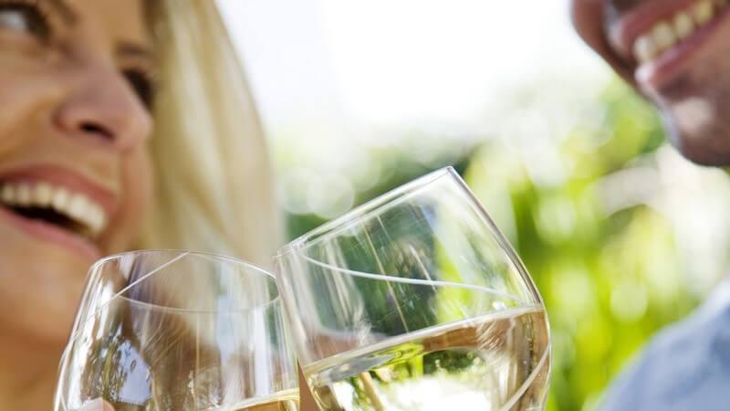 Sie und er im Garten, stoßen mit zwei Gläsern Wein an, lachen sich dabei an