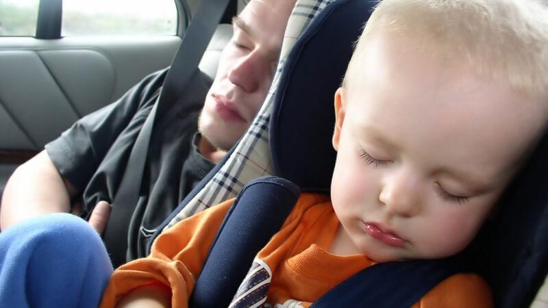 Kind im Autokindersitz schläft, dahinter schläft junger Mann im Auto