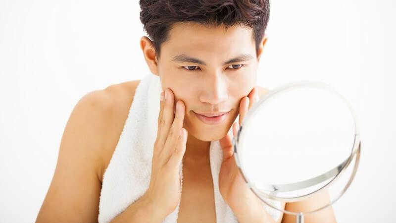 Junger asiatischer Mann mit Handtuch um den Hals betrachtet sich im Kosmetikspiegel und streicht sich über das Gesicht